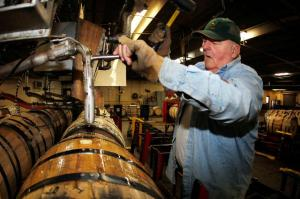 """John """"Bull"""" McCray, a Four Roses Distillery LLC employee, fills white oak barrels with Four Roses bourbon whiskey that will be aged at their warehouse in Cox's Creek, Kentucky, U.S. Since 2002, when the label was bought by Kirin Holdings Co. from Diageo Plc and Pernod-Ricard SA, the distillery has been focused solely on making premium bourbon for the U.S. and overseas markets. Photographer: John Sommers II /Bloomberg."""